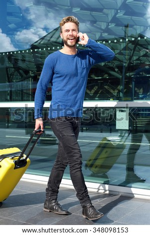Full length portrait of a smiling man traveling with suitcase and cellphone - stock photo