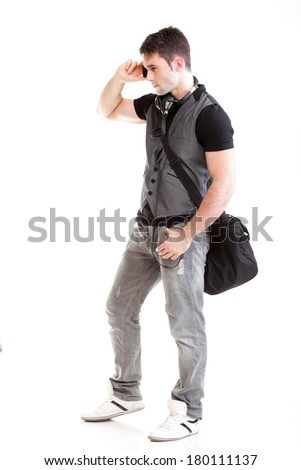 Full length portrait of a smiling school boy holding books and talking on a phone isolated on white background - stock photo