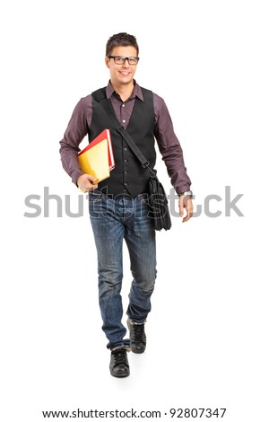 Full length portrait of a smiling school boy walking and holding books isolated on white background - stock photo