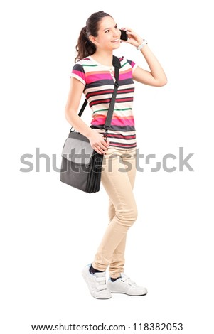 Full length portrait of a smiling school girl with shoulder bag talking on a phone isolated on white background - stock photo
