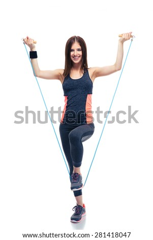 Full length portrait of a smiling sporty woman standing with jumping rope isolated on a white background. Looking at camera - stock photo