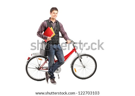 Full length portrait of a smiling student holding books next to a bike isolated on white background - stock photo
