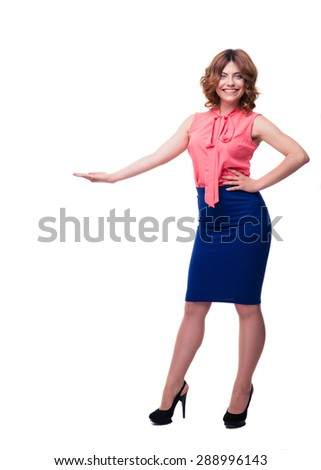 Full length portrait of a smiling woman demonstrating something isolated on a white background. Looking at camera - stock photo