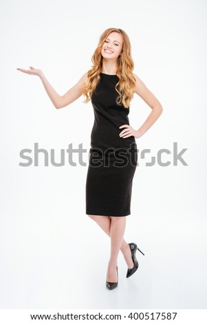 Full length portrait of a smiling woman holding copyspace on the palms isolated on a white background - stock photo