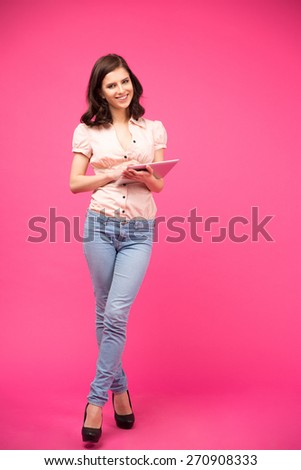 Full length portrait of a smiling woman holding tablet computer over pink background and looking at camera. Wearing in shirt and jeans - stock photo