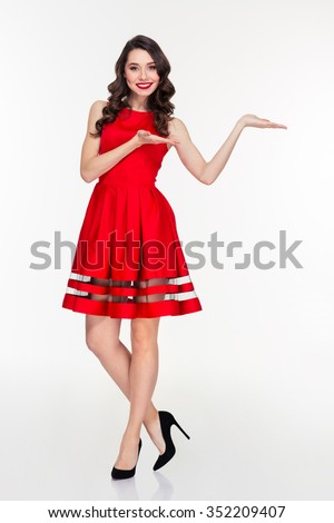 Full length portrait of a smiling woman in red dress holding copyspace on the palms isolated on a white background - stock photo