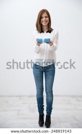 Full length portrait of a smiling woman standing with gift - stock photo