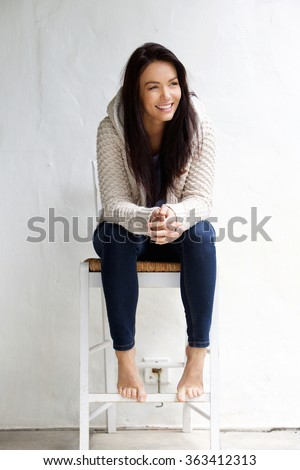 Full length portrait of a smiling young woman sitting on chair - stock photo