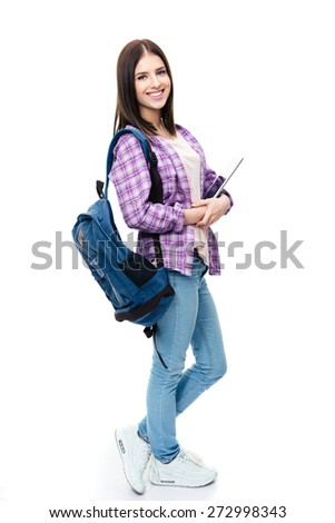 Full length portrait of a smiling young woman standing with backpack and tablet computer. Looking at camera - stock photo