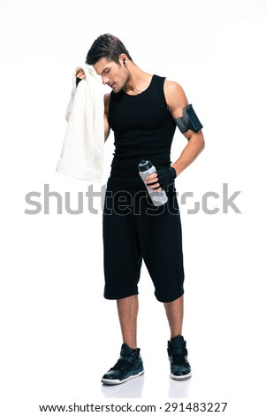 Full length portrait of a sports man holding towel and bottle with water isolated on a white background - stock photo