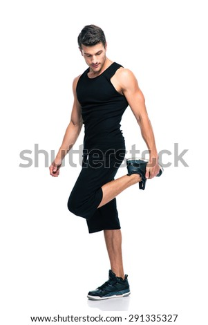 Full length portrait of a sports man stretching legs isolated on a white background - stock photo