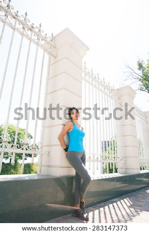 Full length portrait of a sporty woman leaning on the fence outdoors  - stock photo