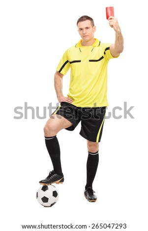 Full length portrait of a strict football referee standing over a ball and showing a red card isolated on white background - stock photo