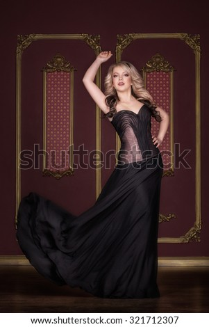 Full length portrait of a stunning woman with long hair, standing in a dark red room wearing long black evening dress posing and looking at the camera - stock photo