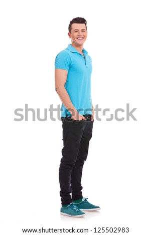 Full length portrait of a stylish young man standing with hands in pockets and looking at the camera over white background - stock photo