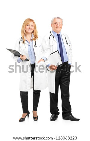 Full length portrait of a team of doctors holding a clipboard and posing isolated on white background - stock photo