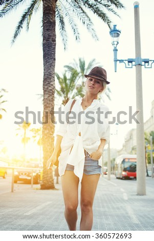 Full length portrait of a trendy young woman dressed in stylish clothes walking in urban scene in sunny summer day, attractive female tourist with classy look standing against sunset and palm trees - stock photo