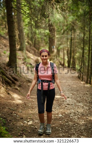 Full length portrait of a woman hiker in the fir forest - stock photo