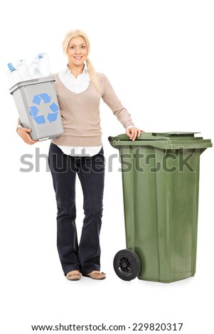 Full length portrait of a woman holding a recycle bin and standing by a large trash can isolated on white background - stock photo