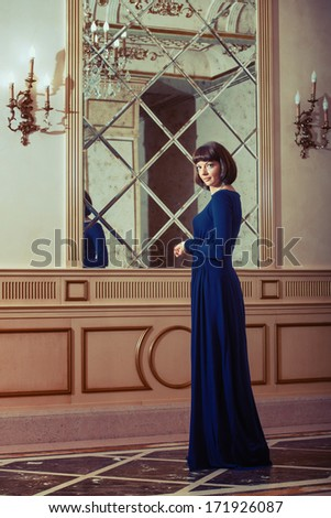 Full-length portrait of a woman in blue evening dress in luxury interior - stock photo