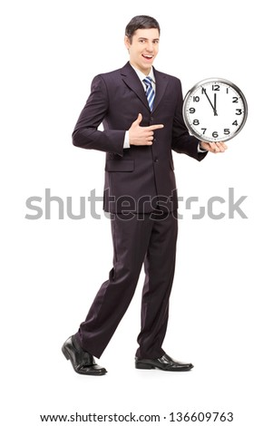 Full length portrait of a youn man in suit pointing on a clock, isolated on white background - stock photo