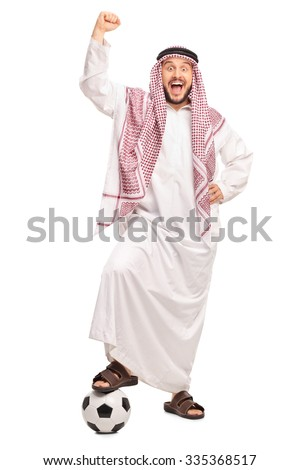 Full length portrait of a young Arab stepping over a football and gesturing happiness isolated on white background - stock photo