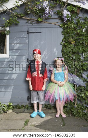 Full length portrait of a young boy in pirate costume and girl in fairy costume by shed - stock photo