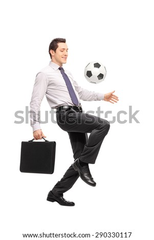 Full length portrait of a young businessman holding a briefcase and juggling a football isolated on white background - stock photo