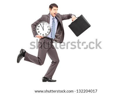 Full length portrait of a young businessman running late with a clock and a briefcase isolated on white background - stock photo