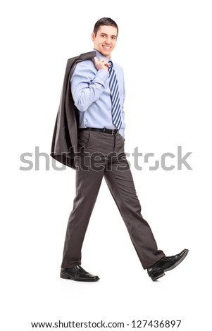 Full length portrait of a young businessman walking with a coat over shoulder isolated on white background - stock photo