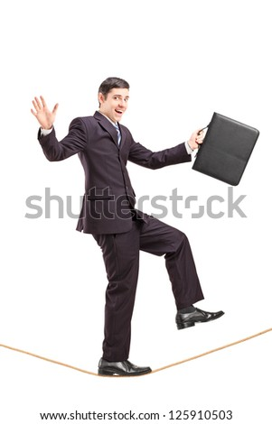 Full length portrait of a young businessman with briefcase walking on a rope isolated on white background - stock photo