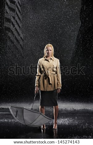 Full length portrait of a young businesswoman holding umbrella upside down in rain  - stock photo