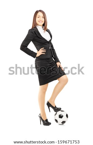 Full length portrait of a young businesswoman in high heels posing with a soccer ball isolated on white background - stock photo