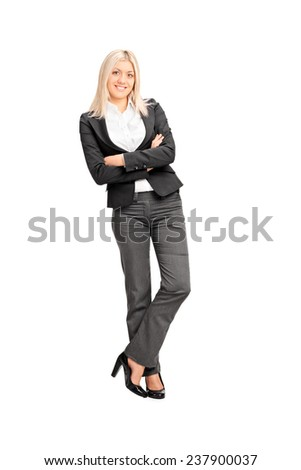 Full length portrait of a young businesswoman leaning against a wall isolated on white background - stock photo