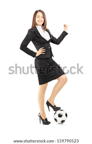 Full length portrait of a young businesswoman posing with a soccer ball and giving thumb up, isolated on white background - stock photo