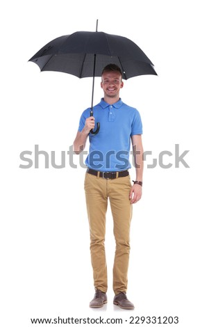 full length portrait of a young casual man holding a black umbrella and smiling for the camera. isolated on a white background - stock photo