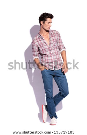 full length portrait of a young casual man standing with his legs crossed and a hand in his pocket while looking away from the camera - stock photo