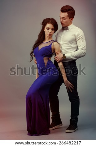 Full length portrait of a young fashionable couple.beautiful couple. A guy hugs a girl. beautiful fashionable couple in the studio - stock photo