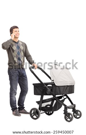 Full length portrait of a young father talking on phone and pushing a baby stroller isolated on white background - stock photo