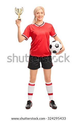 Full length portrait of a young female soccer player holding a ball and a golden trophy isolated on white background - stock photo