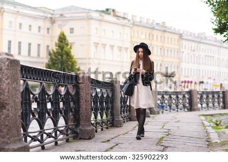 Full length portrait of a young female tourist using smart phone for navigation during walking on the street in urban setting, attractive brunette woman reading message on her cell telephone  - stock photo