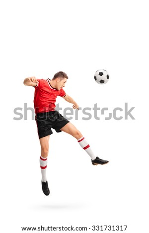 Full length portrait of a young football player heading a ball shot in mid-air isolated on white background - stock photo