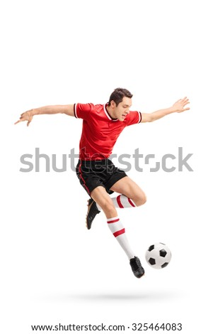 Full length portrait of a young football player in red jersey kicking a ball in mid-air isolated on white background - stock photo