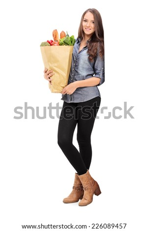 Full length portrait of a young girl holding a grocery bag isolated on white background - stock photo