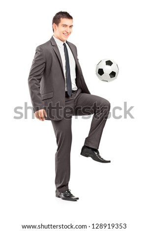 Full length portrait of a young handsome businessman kicking a football isolated on white background - stock photo