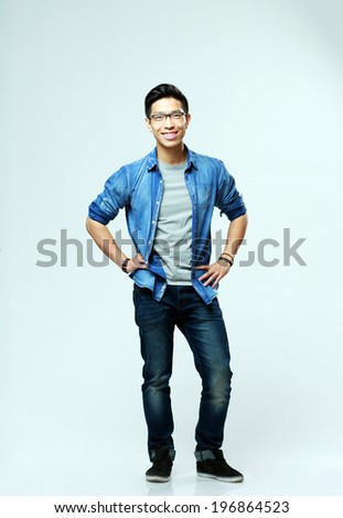 Full-length portrait of a young happy asian man on gray background - stock photo