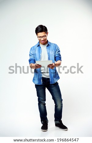 Full length portrait of a young happy man standing with laptop on gray background - stock photo