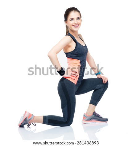 Full length portrait of a young happy sporty woman stretching isolated on a white background. Looking at camera - stock photo