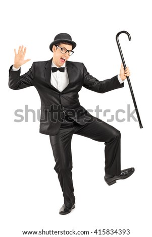 Full length portrait of a young male comedian dancing with a cane isolated on white background - stock photo