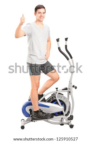 Full length portrait of a young man exercising on a cross trainer machine and giving thumb up isolated on white - stock photo